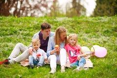 Gl?ckliche Familie auf Picknick im gebl?hten Park, der auf Gras, Elternschaftsfreizeit in der Natur sitzt stockfoto