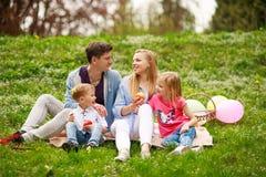 Gl?ckliche Familie auf Picknick im gebl?hten Park, der auf Gras, Elternschaftsfreizeit in der Natur sitzt stockfotos