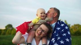 Gl?ckliche Familie, die amerikanische Flagge im Park an einem sonnigen Tag h?lt Im Freienportrait Unabh?ngigkeitstag, am 4 stock footage