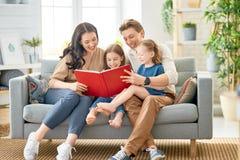 Gl?ckliche Familie, die zu Hause spielt lizenzfreie stockfotos