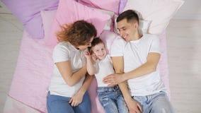 Gl?ckliche Familie im Bett, Mutter, Sohn und Vati sind zusammen k?ssend und umarmend stock footage