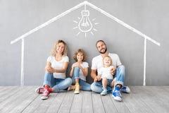 Gl?ckliche Familie mit zwei Kindern, die in neues Haus spielen lizenzfreie stockbilder