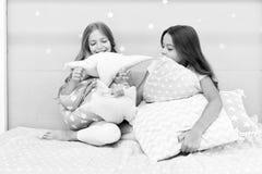 Gl?ckliche Freunde der M?dchen mit netten Kissen Kissenschlachtpyjamapartei Sleepoverzeit f?r Kissenschlacht Handeln was auch imm stockbild