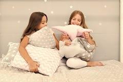 Gl?ckliche Freunde der M?dchen mit netten Kissen Kissenschlachtpyjamapartei Sleepoverzeit f?r Kissenschlacht Handeln was auch imm stockbilder