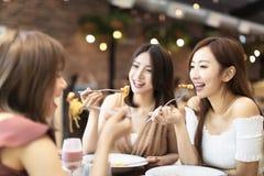 Gl?ckliche Freunde, die im Restaurant zu Abend essen lizenzfreie stockfotos