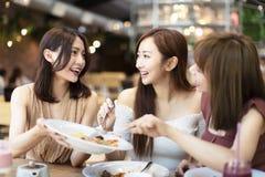 Gl?ckliche Freunde, die im Restaurant zu Abend essen stockfotografie