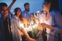 Gl?ckliche Freunde mit Getr?nken r?stend an der Dachspitzenpartei nachts lizenzfreie stockfotografie