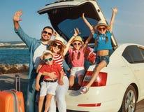 Gl?ckliche gro?e Familie Sommerin der selbstreisereise mit dem Auto auf Strand stockfotografie
