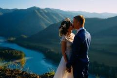 Gl?ckliche Hochzeitspaare, die ?ber der sch?nen Landschaft mit Bergen bleiben lizenzfreie stockfotografie