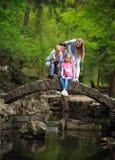 Gl?ckliche junge Familie mit Kindern im gr?nen Park des Sommers auf Steinbr?cke ?ber dem Fluss im Wald stockbilder