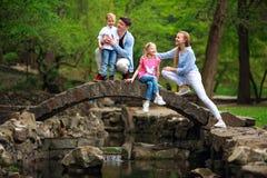 Gl?ckliche junge Familie mit Kindern im gr?nen Park des Sommers auf Steinbr?cke ?ber dem Fluss im Wald lizenzfreies stockfoto