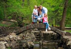 Gl?ckliche junge Familie mit Kindern im gr?nen Park des Sommers auf Steinbr?cke ?ber dem Fluss im Wald lizenzfreie stockfotos