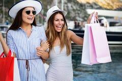 Gl?ckliche junge Frauen mit Einkaufstaschen genie?end im Einkaufen Verbraucherschutzbewegung, Einkaufen, Lebensstilkonzept lizenzfreie stockfotos