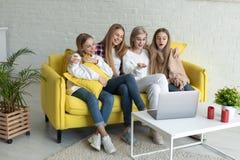 Gl?ckliche junge lesbische Paare mit T?chtern in der zuf?lligen Kleidung, die zusammen zu Hause auf gelbem Sofa sitzt lizenzfreie stockfotos