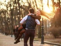 Gl?ckliche junge Paare in den Liebesjungverm?hlten, die froh Spa? im Stadtpark haben lizenzfreies stockbild