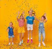 Gl?ckliche Kinder an den Feiertagen, die in mehrfarbige Konfettis auf Gelb springen lizenzfreie stockbilder