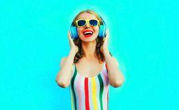 Gl?ckliche l?chelnde Frau des Portr?ts, die Musik in den drahtlosen Kopfh?rern auf buntem Blau h?rt stockfoto