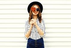 Gl?ckliche l?chelnde junge Frau des Portr?ts, die ihr Auge mit geformtem Lutscher des roten Herzens im schwarzen runden Hut, wei? stockbilder