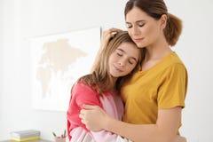 Gl?ckliche Mutter, die ihre Jugendlichtochter umarmt lizenzfreie stockbilder