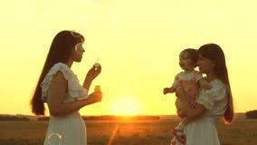 Gl?ckliche Mutter, die mit den Kindern durchbrennen Seifenblasen spielt Töchter freuen sich und lächeln, Blasen fliegen in Park b stock footage