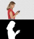 Gl?ckliche nette sch?ne Spielspiele der jungen Frau durch Handy, Alpha Channel stockfoto