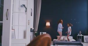 Gl?ckliche nette Tochter und junge die Mutter, die auf Bettwann springt und tanzt, haben Spa? w?hrend der Feiertage zu Hause stock footage