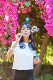 Gl?ckliche sch?ne Schlagseifenblasen der jungen Frau im Freien lizenzfreie stockfotos