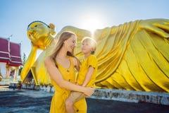 Gl?ckliche Touristen Mutter und Sohn auf dem Hintergrund, der Buddha-Statue ofLying ist stockfoto