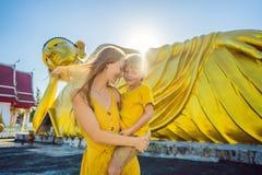 Gl?ckliche Touristen Mutter und Sohn auf dem Hintergrund, der Buddha-Statue ofLying ist stockfotos