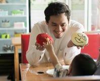 Gl?cklicher asiatischer Vater und sein todler, die zusammen Zeit nach innen am Kuchenspeicher und -caf? verbringt stockbilder