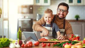 Gl?cklicher Familienvater mit dem Sohn, der Gem?sesalat zubereitet lizenzfreie stockfotografie