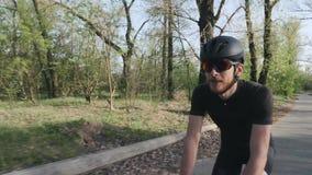 Gl?cklicher froher l?chelnder Radfahrer beim Fahren von Fahrrad im Park Radfahrer, der schwarzen Ausstattungssturzhelm und -Sonne stock video