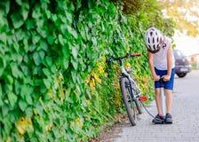 Gl?cklicher kleines Kinderjunge im wei?en Sturzhelm, der Reifen in seinem Fahrrad aufbl?st stockfotografie