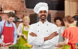 Gl?cklicher m?nnlicher indischer Chef im Toque am Kochkurs stockfoto
