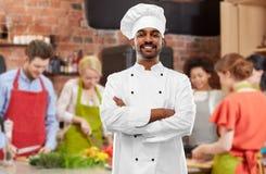 Gl?cklicher m?nnlicher indischer Chef im Toque am Kochkurs stockfotografie