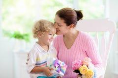 Gl?cklicher Muttertag Kind mit Geschenk f?r Mutter lizenzfreie stockfotografie