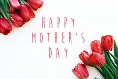 Gl?cklicher Muttertagtext und sch?ne rote Tulpen auf dem wei?en h?lzernen flachen Hintergrund legen Gl?ckliche Muttertagesgru?kar