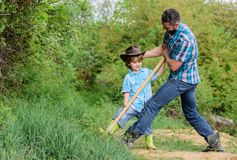 Gl?cklicher Tag der Erde Graben Sie grounf mit Schaufel reicher Untergrund Eco-Bauernhof ranch kleiner Jungenkinderhilfsvater im  lizenzfreie stockfotos