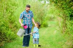 Gl?cklicher Tag der Erde Nursering Stammbaum Eco-Bauernhof kleiner Jungenkinderhilfsvater bei der Landwirtschaft Benutzen Sie Gie lizenzfreies stockfoto