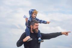Gl?cklicher Vatertag Vati und Sohn spielen auf Himmelhintergrund Vater und Sohn, die zusammen ein Papierflugzeug errichten stockbild