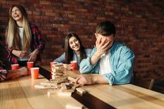 Gl?ckliches Freundspielgesellschaftsspiel am Tisch im Caf? stockfotografie