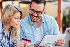 Gl?ckliches junges Paareinkaufen online beim Sitzen in einem Caf? stockfotos