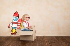 Gl?ckliches Kind, das zu Hause mit Spielzeugrakete spielt lizenzfreie stockfotos