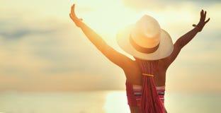 Gl?ckliches Kinderm?dchen im Badeanzug und in Hut, die auf Strand bei Sonnenuntergang sitzen stockbild