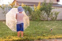 Gl?ckliches Kindheitkonzept Sommerferien mit Kindern Automatisches Betriebsbew?sserungssystem Vorsch?ler, der Spa? auf Front hat stockbild