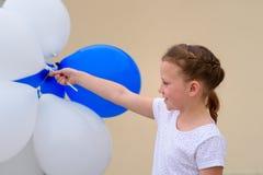 Gl?ckliches kleines M?dchen mit den blauen und wei?en Ballonen stockfotografie