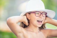 Gl?ckliches l?chelndes M?dchen mit zahnmedizinischen Klammern und Gl?sern Orthodontist- und Zahnarztkonzept stockfotografie