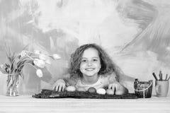Gl?ckliches Ostern-M?dchen mit Bleistiften, bunten Eiern und Tulpenblumen stockfoto