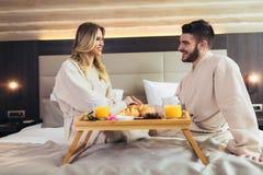Gl?ckliches Paar, das im Luxushotelraum fr?hst?ckt stockfoto