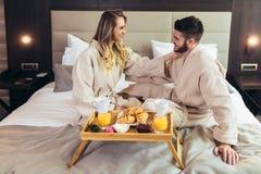 Gl?ckliches Paar, das im Luxushotelraum fr?hst?ckt stockfotografie